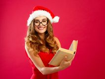 Young attractive Santa girl in red dress holding book over red b Royalty Free Stock Images