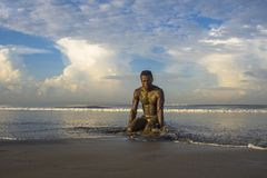 Young attractive and sexy black African American man with sexy muscular body kneeling on beautiful tropical desert beach enjoying stock photo