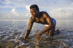 Young attractive and sexy black afro American man with athletic muscular body posing cool in sea water on desert beach in male. Artistic expressive portrait of royalty free stock images