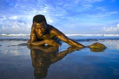 Young attractive and sexy black afro American man with athletic muscular body posing cool in sea water on desert beach in male. Artistic expressive portrait of royalty free stock photography