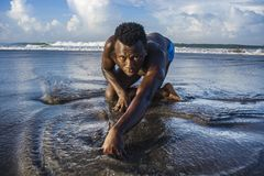 Young attractive and sexy black afro American man with athletic muscular body posing cool in sea water on desert beach in male. Artistic expressive portrait of stock photo