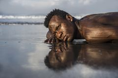 Young attractive and sexy black afro American man with athletic muscular body posing cool in sea water on desert beach in male. Artistic expressive portrait of royalty free stock photo
