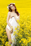 Young attractive sexy girl on a sunny day of flowering rape field with flowers in red hair Royalty Free Stock Photography