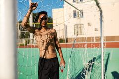 Young attractive shirtless African American sportsman standing in football goal after game at stadium
