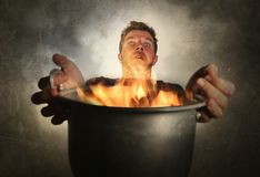 Young attractive and shocked messy home cook man with apron holding cooking pot in fire burning the food in kitchen disaster. And unskilled and terrible royalty free stock photo