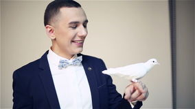 Young attractive showman holding a white pigeon on hand. Domesticated bird sitting on the hand of the illusionist. Photo-session at the studio. Slow motion stock video footage
