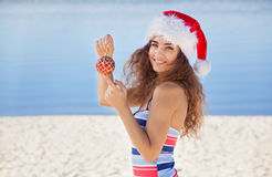 Young, attractive, slender girl in a bathing suit and hat of Santa Claus on the beach holding a red Christmas ball. Royalty Free Stock Photos
