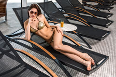 Young attractive slim girl in bikini relaxing on deck chair in wellness spa hotel resort Royalty Free Stock Image