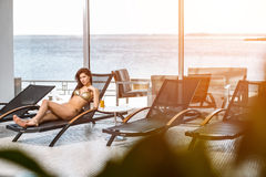 Young attractive slim girl in bikini relaxing on deck chair in wellness spa hotel resort Royalty Free Stock Images