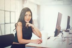 Young attractive smart woman in casual office outfit sitting in. Front of computer over creative office background stock image