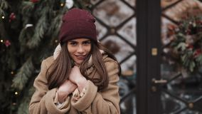 Young attractive smiling brunette girl wearing winter hat and scarf warming her hands, looking to camera. Woman waiting stock video footage