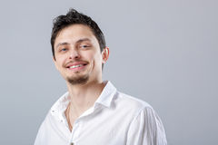 Young attractive smiling brunette man in white shirt on gray bac Stock Photo