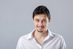 Young attractive smiling brunette man in white shirt on gray  Stock Photo