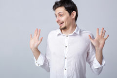 Young attractive smiling brunette man in white shirt on gray  Stock Photos