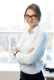 Young Attractive Smiling Businesswoman in White in Bright Modern Office Royalty Free Stock Photography