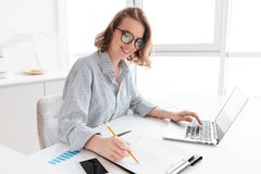 Young attractive smiling girl in glasses and striped shirt worki Stock Photography