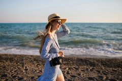 Young attractive smiling girl walking along the beach stock photos