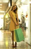 Young Attractive Smiling Girl in Yellow Dress is Walking in the Mall with Shopping Bags Royalty Free Stock Photos