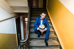 Young attractive smiling man in blue suit sitting on stairs with bouquet, indoor shot Royalty Free Stock Photo