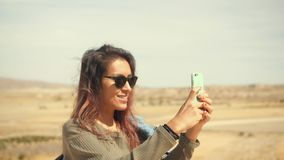Young Attractive Smiling Mixed Race Girl Takes Panoramic Photo of Desert on a Mobile Phone. Happy Tourist Woman in Sunglases stock video
