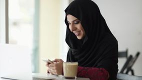 Young attractive smiling muslim woman in hijab sitting in the cafe and typing a message on her mobile phone. Laptop and. A glass with cappuccino on the table stock video