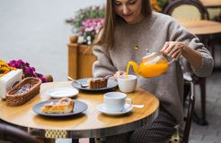 Young attractive smiling woman in gray knitted sweater drinking tea outdoors at the street cafe stock image