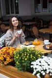 Young attractive smiling woman in gray knitted sweater drinking tea outdoors at the street cafe royalty free stock image