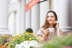 Young attractive smiling woman in gray knitted sweater drinking tea outdoors at the street cafe stock images