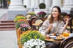 Young attractive smiling woman in gray knitted sweater drinking tea outdoors at the street cafe stock photos