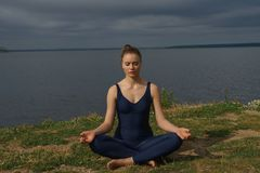 Young attractive smiling woman practicing yoga, sitting in Half Lotus exercise, Ardha Padmasana pose stock photography