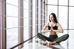 Young attractive smiling woman practicing yoga, sitting in Half Lotus exercise, Ardha Padmasana pose. Young attractive smiling woman practicing yoga, sitting in Royalty Free Stock Images