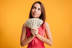 Young attractive smiling woman thinking how to spend her bunch o. F money, isolated on yellow background Royalty Free Stock Images
