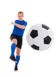 Young attractive soccer player in blue uniform kicking ball isol Royalty Free Stock Images