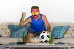 Young attractive Spanish man happy and excited watching football match on TV celebrating victory goal crazy with Spain flag painte. D colors in his face cheering Stock Photo