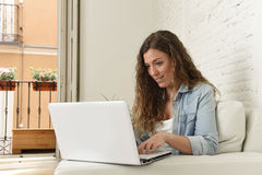 Young attractive spanish woman using laptop computer sitting relaxed working on home couch. Young attractive spanish woman in denim casual clothes using laptop Royalty Free Stock Photos