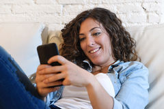 Young attractive spanish woman using mobile phone app or texting on home couch. Young attractive spanish woman in denim casual clothes using mobile phone app or Stock Image