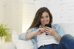 Young attractive spanish woman using mobile phone app or texting on home couch Royalty Free Stock Photos