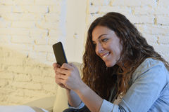 Young attractive spanish woman using mobile phone app or texting on home couch Stock Photos