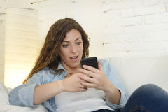 Young attractive spanish woman using mobile phone app or texting on home couch Stock Photography