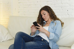 Young attractive spanish woman using mobile phone app or texting on home couch Royalty Free Stock Photo