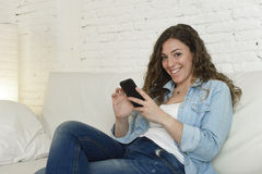 Young attractive spanish woman using mobile phone app or texting on home couch. Young attractive spanish woman in denim casual clothes using mobile phone app or Royalty Free Stock Photography