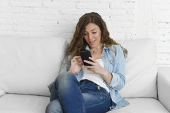 Young attractive spanish woman using mobile phone app or texting on home couch Royalty Free Stock Image