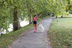 Young attractive sport girl running with dog in park.  Royalty Free Stock Photo