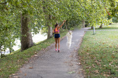 Young attractive sport girl running with dog in park Stock Images