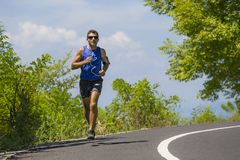 Young attractive sport runner man training in asphalt road running workout a sunny Summer morning surrounded by trees and vegetati royalty free stock photo