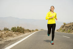 Young attractive sport woman running on asphalt road with desert mountain landscape background Stock Photos