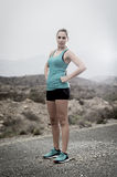 Young attractive sport woman in running singlet and shorts posing defiant and cool in asphalt road in front of mountain Royalty Free Stock Photos