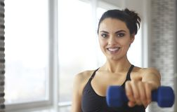 Young sportswoman doing fitness exercises at sport gym stock image