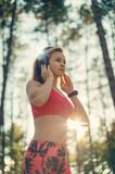 Young attractive sportswoman listening to music wearing headphones. Sport, fitness, workout. Stock Photo