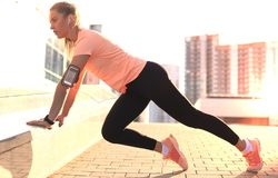 Young attractive sporty girl doing push ups, outdoors at sunset or sunrise in city. royalty free stock photo